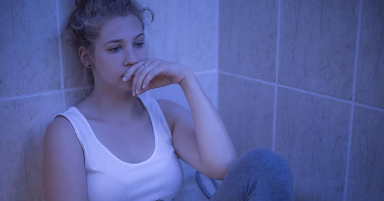 junge Frau ist nachdenklich wegen Schmerzen beim Sex nach